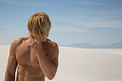 blond man without a shirt in the desert rubbing his eye