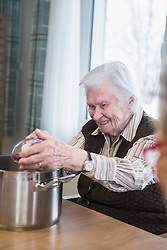 Senior woman cooking in rest home