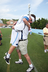 09 May 2009: North Carolina Tar Heels attackman Billy Bitter (4) is hugged by his head coach Joe Breschi after a 15-13 win over the University of Maryland - Baltimore County Retrievers on Fetzer Field in Chapel Hill, NC.