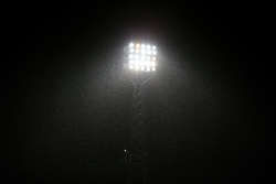 General view of the ground before the game as rain falls past the floodlights