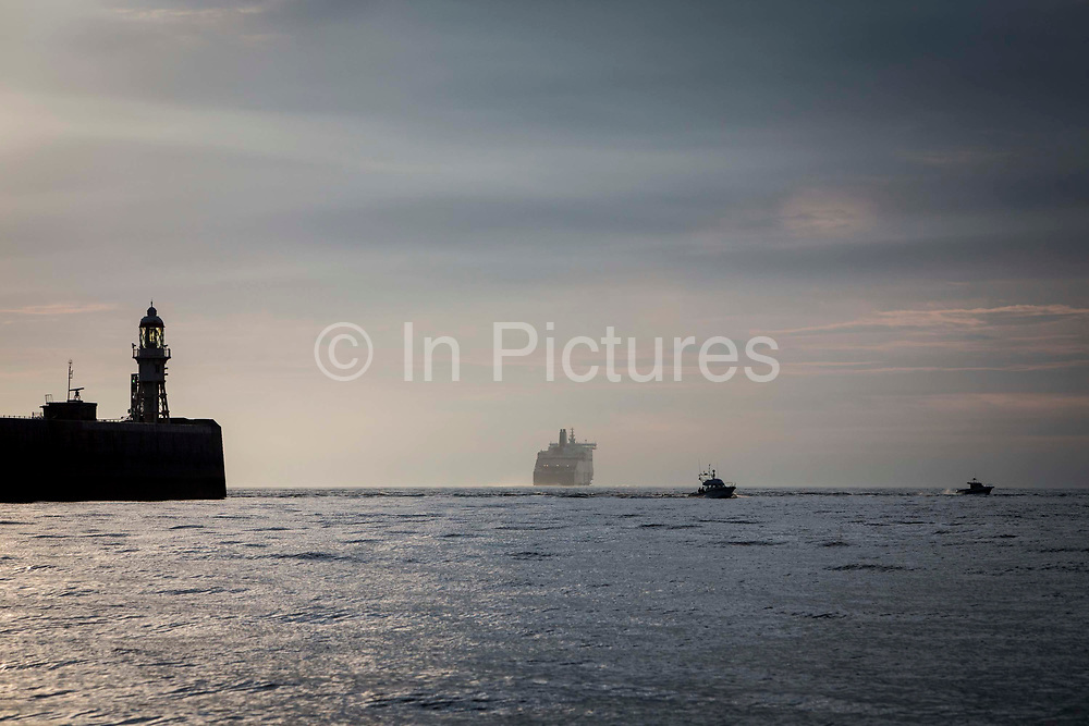 A ferry boat and two motorboats sail on the English Channel out of Dover Harbour in the early morning, Kent, England, United Kingdom.