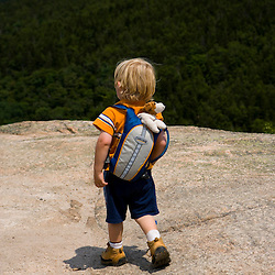 A young boy hiking in Acadia National Park Maine USA
