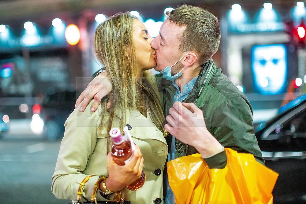 © Licensed to London News Pictures. 10/10/2020. Manchester, UK. Having just come out of Sainsbury's , couple ALEX CHICK (25) and FREDDY PHILLIPS (23) are celebrating after Freddy proposed to Alex this evening . People queue outside Sainsbury's on Deansgate as venues close and people come out on to the street . People out in pubs, bars and restaurants in Manchester City Centre ahead of the currently imposed daily 10pm curfew . Millions of people across the north of England are waiting to learn if the British Government will impose a regional lockdown on Monday (12th October 2020), as Coronovirus infection rates continue to rise rapidly . Photo credit: Joel Goodman/LNP
