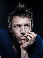 studio portrait on black background of a funny expressive caucasian man frowning sad