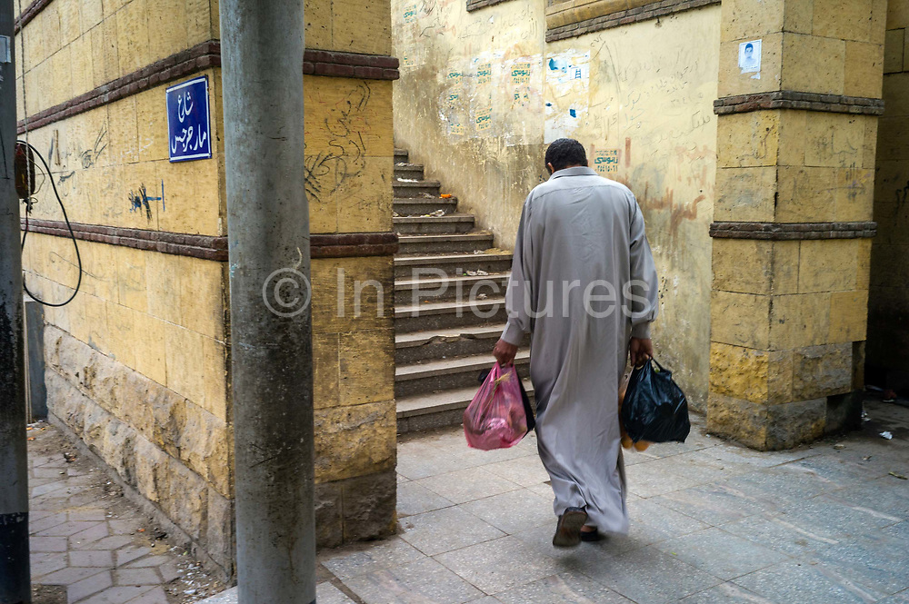 A man carrying bags of shopping walks towards steps on a Cairo street.