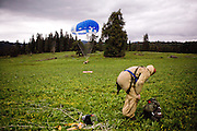 Frankie Romero lands in an open field near the McCall smokejumper base in McCall, ID while another smokejumper removes his gear in a simulation of what it would be like during an actual fire.