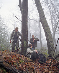 three men hiking and hanging out together in the woods during the winter