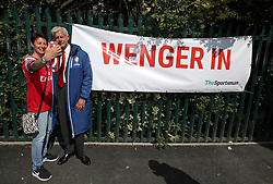 A fan takes a selfie with an Arsene Wenger lookalike, standing next to a Wenger In banner, during the Emirates FA Cup Final at Wembley Stadium, London.