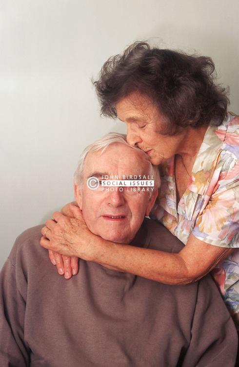 Elderly couple hugging,