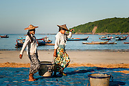 Myanmar, Ngapali. Two woman carry a big basket full of fish.<br />  Every single morning all the fisherman from the little village at Ngapali Beach come back home with their night catch. At the beach all the women wait for them and afterwards work with drying and selling fish and other creatures from the sea begins.