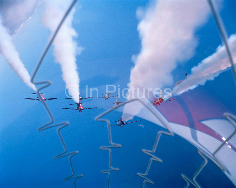 Seen from the cockpit of another Hawk of the elite 'Red Arrows', Britain's Royal Air Force aerobatic team during an In-Season Practice (ISP) training flight near their base at RAF Scampton. Seen through the explosive Plexiglass cockpit of a tenth plane, we see forward into deep blue sky as two sets of aerobatic pilots steer their aircraft before a crossover manoeuvre, their organic white smoke pouring from their jet pipes to emphasize their paths through the air. In front of a local crowd at the airfield the team work their way through a 25-minute series of display manoeuvres that are loved by thousands at summer air shows. After some time off, spare days like this are used to hone their manual aerobatic and piloting skills before re-joining the air show circuit. Since 1965 they've flown over 4,000 shows in 52 countries.
