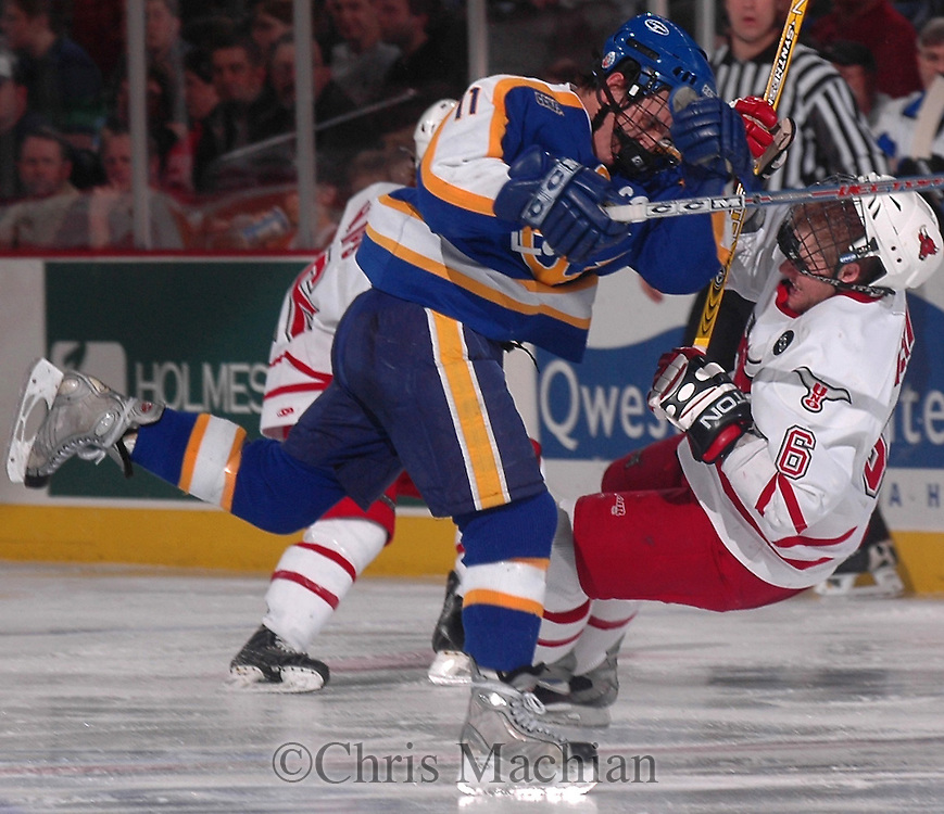 """3/11/05 Omaha Neb. Lake Superior State's Trent Campbell checks University of  Nebraska at Omaha""""s Mike Eickman  during the third period of Friday nights game at the Qwest Center Omaha. University of  Nebraska at Omaha won the first game of the CCHA play-offs.(chris machian/Prarie Pixel Group)"""