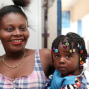 INDIVIDUAL(S) PHOTOGRAPHED: Eme Okon (left) and Favour Okon (right). LOCATION: Epko Abasi Clinic, Calabar, Cross River, Nigeria. CAPTION: A mother waits with her baby to receive their medication in the pharmacy section of the Epko Abasi Clinic. She reports being satisfied with the service.