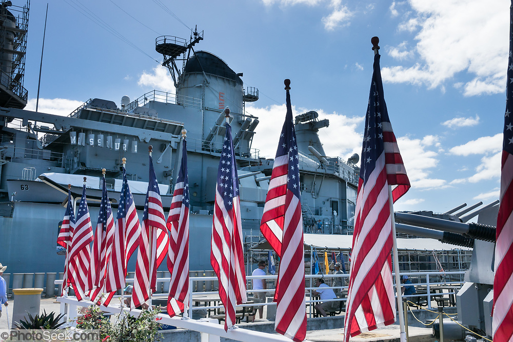 """USA flags at 1944 USS Missouri: ship served WW II, 1950 Korean War, 1991 Desert Storm. Pearl Harbor, Oahu, Hawaii. Ordered in 1940 and active in June 1944, the USS Missouri (""""Mighty Mo"""") was the last battleship commissioned by the United States. She is best remembered as the site of the surrender of the Empire of Japan which ended World War II on September 2, 1945 in Tokyo Bay. In the Pacific Theater of World War II, she fought in the battles of Iwo Jima and Okinawa and shelled the Japanese home islands. She fought in the Korean War from 1950 to 1953. Decommissioned in 1955 into the United States Navy reserve fleets (the """"Mothball Fleet""""), she was reactivated and modernized in 1984 and provided fire support during Operation Desert Storm in January-February 1991. The ship was decommissioned in March 1992. In 1998, she was donated to the USS Missouri Memorial Association and became a museum at Pearl Harbor."""