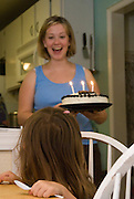 A woman sings happy birthday to her daughter on her third birthday