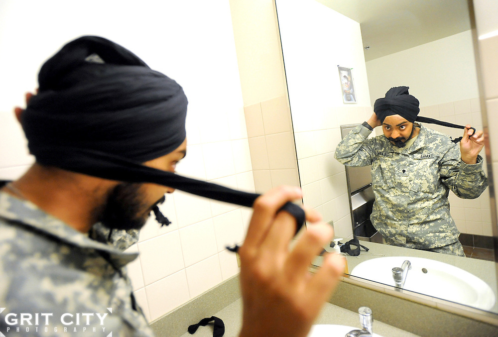 Spc. Simranpreet Singh Lamba, a combat medic with 201st BfSB, demonstrates how he ties a 5-meter-long turban May 23, at the unit headquarters. Lamba, a Sikh whose religion asks that he never cut his hair, says he spends just 7 minutes each morning tying the turban.