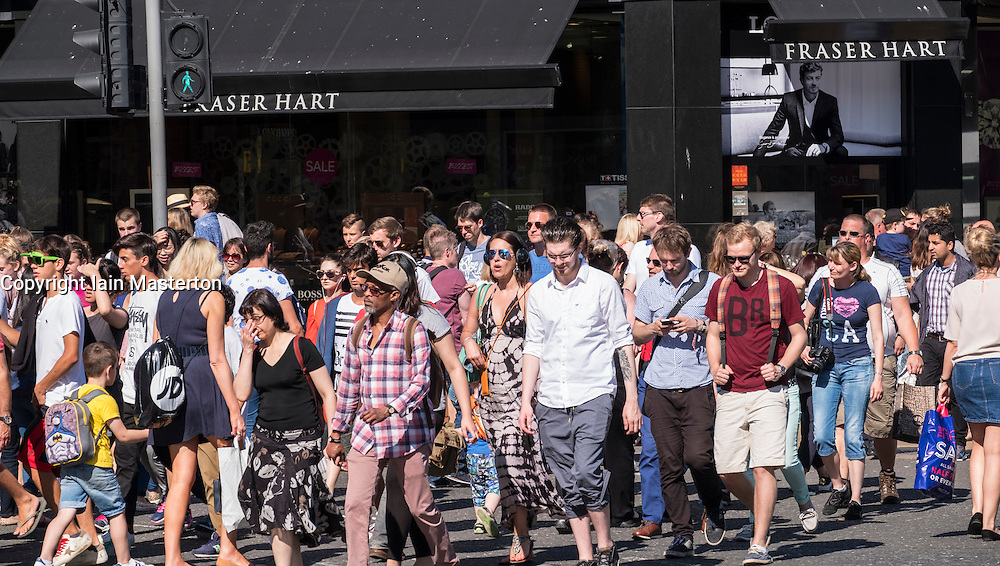Many pedestrians on busy street crossing on Princes Street in Edinburgh, Scotland, united Kingdom