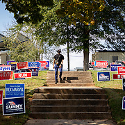 CHARLOTTE, NC - OCT 15: A man walks down steps flanked by political yard signs after voting at Garinger High School on the first day of early voting in Charlotte, North Carolina on October 15, 2020.  Early voting in the state of North Carolina runs from October 15th to October 31st. (Photo by Logan Cyrus for The Washington Post)