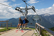 Passengers prepare to leave the chairlift in Velika Planina, on 26th June 2018, in Velika Planina, near Kamnik, Slovenia. Velika Planina is a mountain plateau in the Kamnik–Savinja Alps - a 5.8 square kilometres area 1,500 metres 4,900 feet above sea level. Otherwise known as The Big Pasture Plateau, Velika Planina is a winter skiing destination and hiking route in summer. The herders huts became popular in the early 1930s as holiday cabins known as bajtarstvo but these were were destroyed by the Germans during WW2 and rebuilt right afterwards by Vlasto Kopac in the summer of 1945.