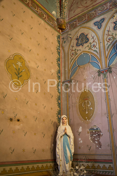 A figurine of Mary and wall decoration in the church of Sant-Michel, on 21st May 2017, in Lagrasse, Languedoc-Rousillon, south of France. Lagrasse is listed as one of Frances most beautiful villages and lies on the famous Route 20 wine route in the Basses-Corbieres region dating to the 13th century.