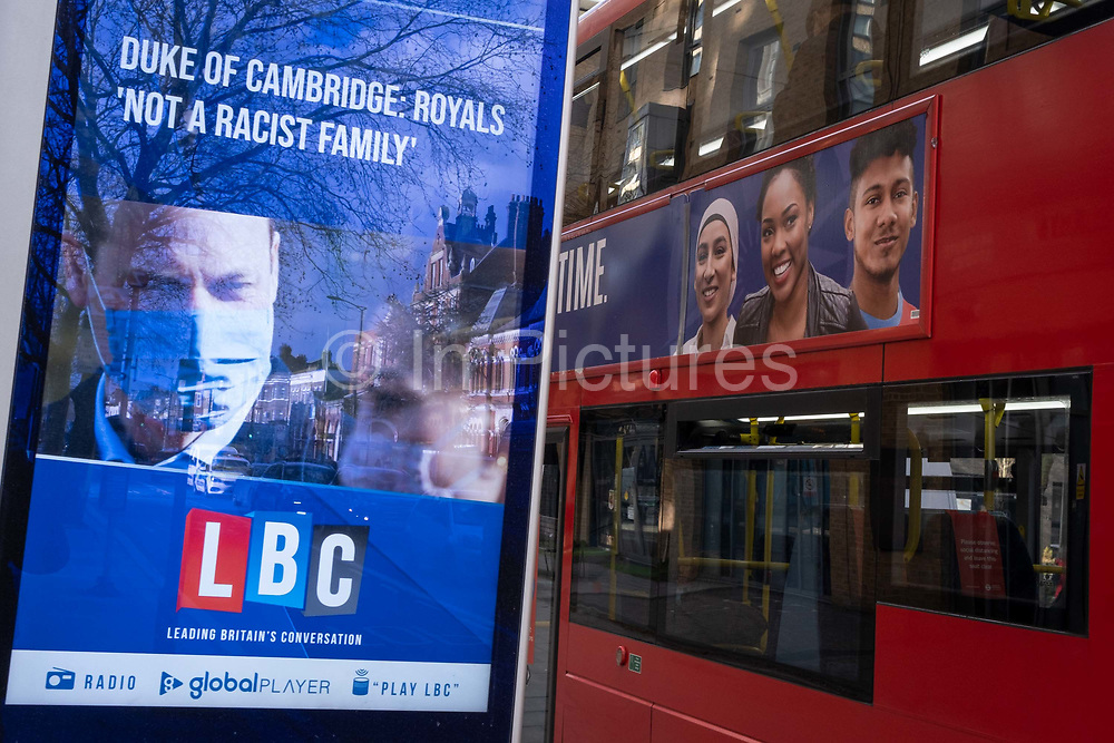 In response to Harry the Duke of Sussex and wife Meghans Oprah interview last weekend, Prince William, a masked Duke of Cambridge responds with a denial, that the royal family is not a racist family, as reported on a digital news screen on the Walworth Road. A bus passes carrying an ad showing a multi-cultural population, on 11th March 2021, in London, England. In the US broadcast interview, both Harry and Meghan complained about racist remarks made by an unnamed family member, about the colour of their future babys skin colour.
