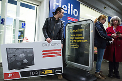 © Licensed to London News Pictures . 27/11/2015 . Salford , UK . A man carrying a 49 inch television from a branch of Tesco in Pendleton , Salford , this morning (Friday 27th November) as people behind queue for Black Friday offers . Last year (2014) scuffles and fights were reported amongst queuing bargain-hunters . Photo credit: Joel Goodman/LNP