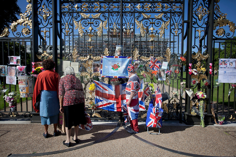 © Licensed to London News Pictures. 31/08/2013. London, UK. Royal fans look at tributes to Diana Princess of Wales outside the gates of Kensington Palace in London today (31/08/2013) on the 16th anniversary of her death in Paris (1997). Photo credit: Matt Cetti-Roberts/LNP