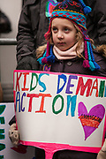 """A girl carries a sign reading """"Kids demand action."""" the sign is in the same bright colors as her hat."""