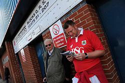 A fan reads a programme outside the Spotland Stadium - Photo mandatory by-line: Dougie Allward/JMP - Mobile: 07966 386802 23/08/2014 - SPORT - FOOTBALL - Manchester - Spotland Stadium - Rochdale AFC v Bristol City - Sky Bet League One
