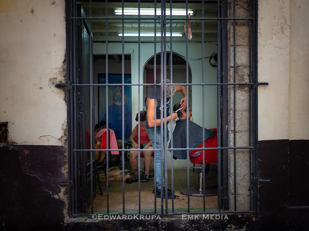 A look inside an  barber shop. in Old Havana, while a woman gets a haircut and a dog sleeps.