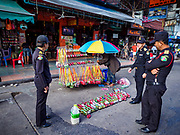01 AUGUST 2018 - BANGKOK, THAILAND: Bangkok code enforcement officers ask a street vender to move out of the right of way on Khao San Road in Bangkok. Khao San Road is Bangkok's original backpacker district and is still a popular hub for travelers, with an active night market and many street food stalls. The Bangkok municipal government went through with it plans to reduce the impact of the street market on August 1 because city officials say the venders, who set up on sidewalks and public streets, pose a threat to public safety and could impede emergency vehicles. Venders are restricted to working from 6PM to midnight and fewer venders will be allowed to set up on the street. It's the latest in a series of night markets and street markets the city has closed.   PHOTO BY JACK KURTZ