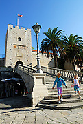 Two children (9 years old, 5 years old) on the stairway at the Revelin Tower and land gate (Kopnena Vrata) entrance into the old town of Korcula. Korcula old town, island of Korcula, Croatia.