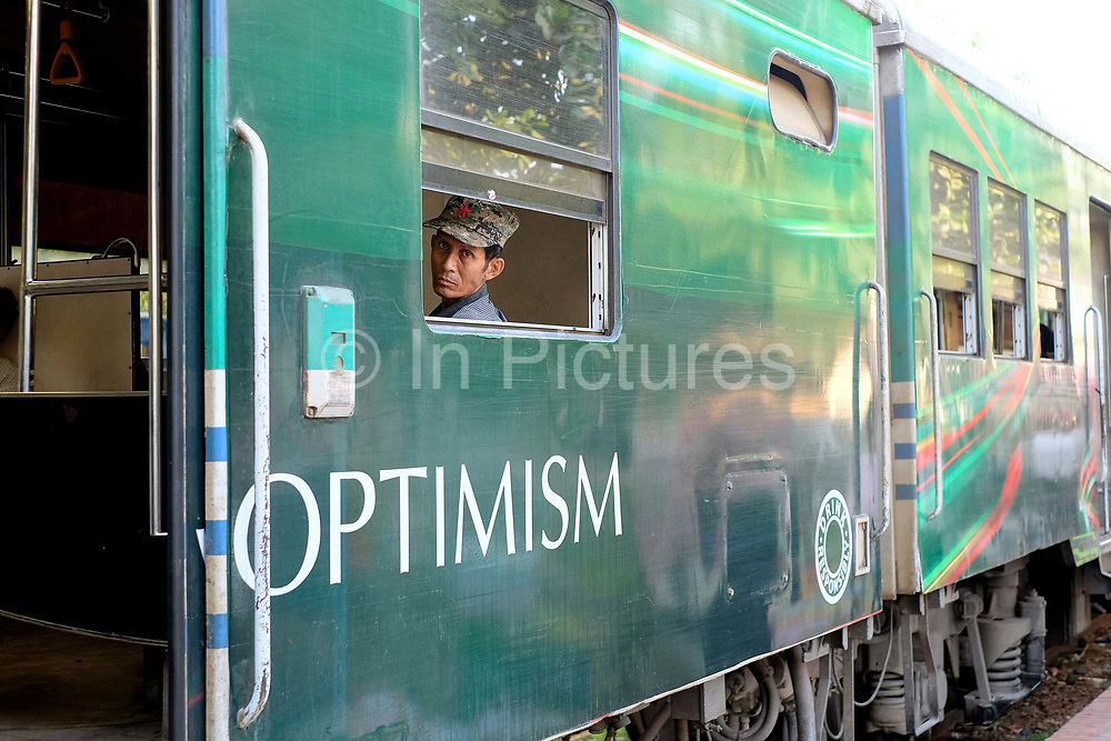 A man looks out of a carriage window at Thamine station on the Circular Railway on 17th May 2016 in Yangon, Myanmar. The railway, a narrow gauge local commuter trail network serving Yangon metropolitan area is a 28.5 mile 45.9 km 39 station loop system. This British built rail-loop connects Yangon to its satellite towns and villages