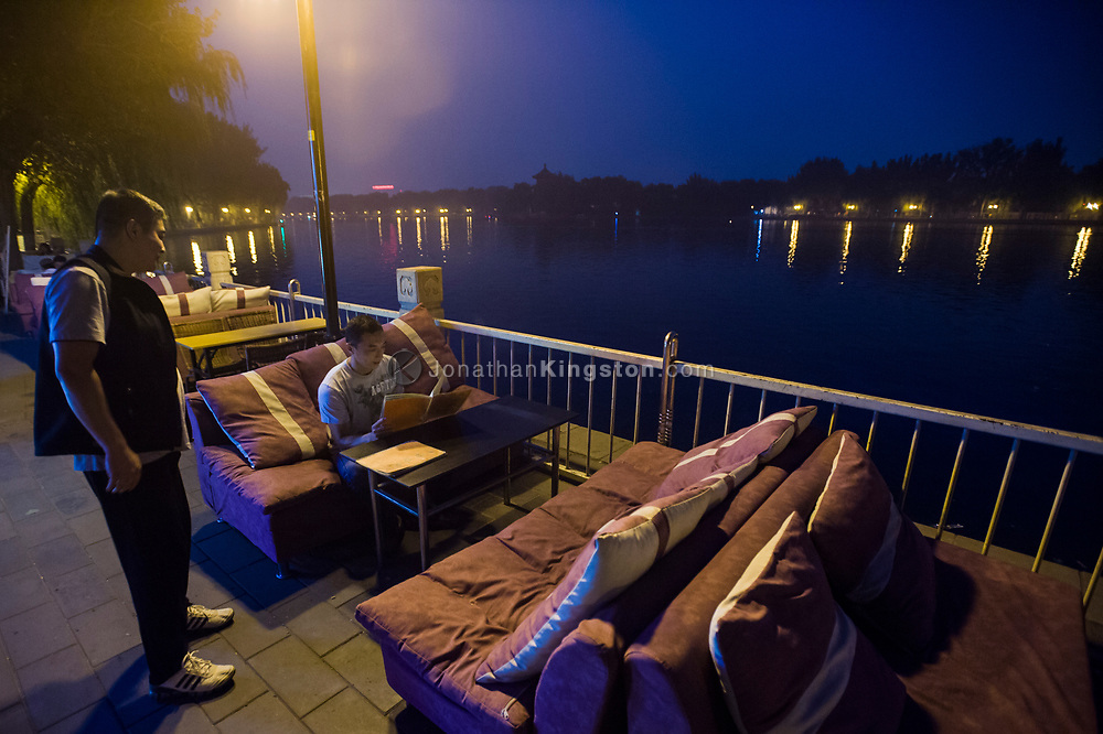 A man orders from a menu at an outdoor restaurant next to Houhai lake in Beijing, China.  The Houhai lake area is famous for its nightlife due to its many restaurants, bars and cafes.