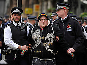 © Licensed to London News Pictures. 11/11/2011. London, UK. A man is handcuffed and led away by police officers.  Police arrest members of the EDL near the Cenotaph following a Remembrance Day service today (11/11/2011). A large group of EDL members where arrested. Police a. Photo credit : Stephen Simpson/LNP