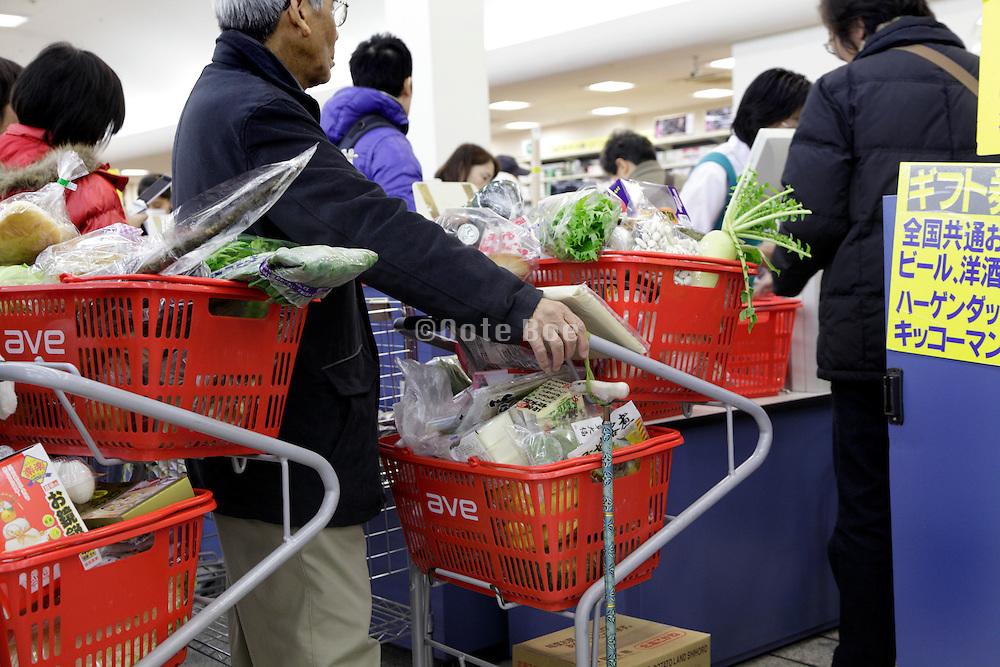 shoppers line up at a supermarket cashier in Tokyo, Japan