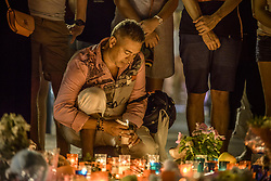August 18, 2017 - Barcelona, Catalonia, Spain - A mourner places a candle at a makeshift memorial on top of the Joan Maro mosaic in Las Ramblas, the site where a van came to a halt after a 550 meter long jihadist terror trip. Thirteen people were killed and almost 80 wounded, 15 seriously, when the van tore through the crowd (Credit Image: © Matthias Oesterle via ZUMA Wire)