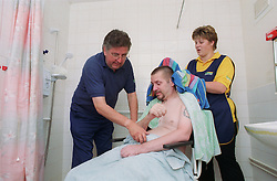 Carers assisting wheelchair user with washing and drying,