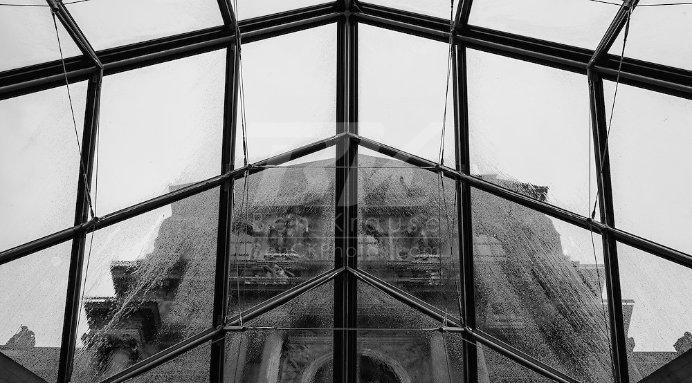 Rain falls on the glass of the pyramid at the Musée du Louvre in Paris, France on May 19, 2012.