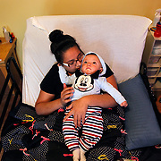 Genesis Flores holds her son Jose Maria, 10 months, while laying on her medical bed May 6 in her home in Mission. Half way through her pregnancy on Easter weekend of April 2012 Flores was visiting family in Reynosa when she was involved in a serious motor vehicle accident that left her paralyzed. Flores was taken to McAllen Medical Center where doctors placed her into a coma and were able to save her and her son. Flores now relies on her family to help her as she tries to raise her child and learn to live with her paralysis. <br /> photo by Nathan Lambrecht/nlambrecht@themonitor.com