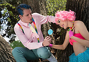 A blue-haired man with a candy tie offers a young woman a tempting lolly pop treat that appears not to appeal to her.
