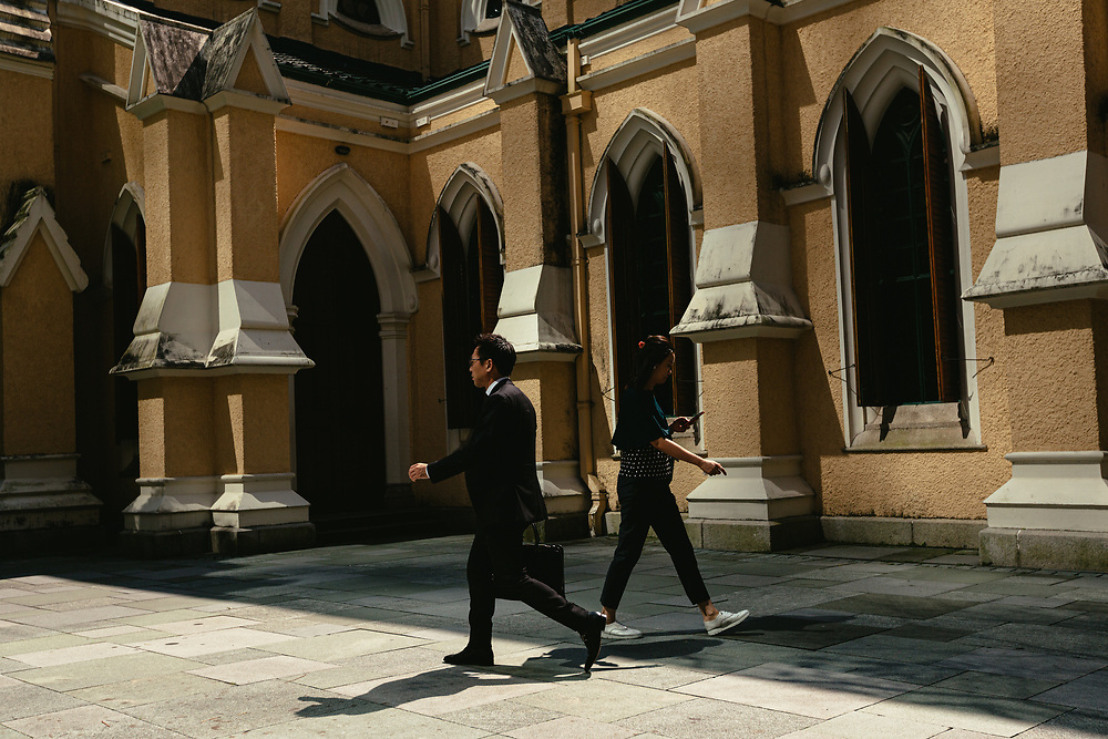 People walk past St. John's Cathedral, in Central, Hong Kong Island, on October 15, 2019.