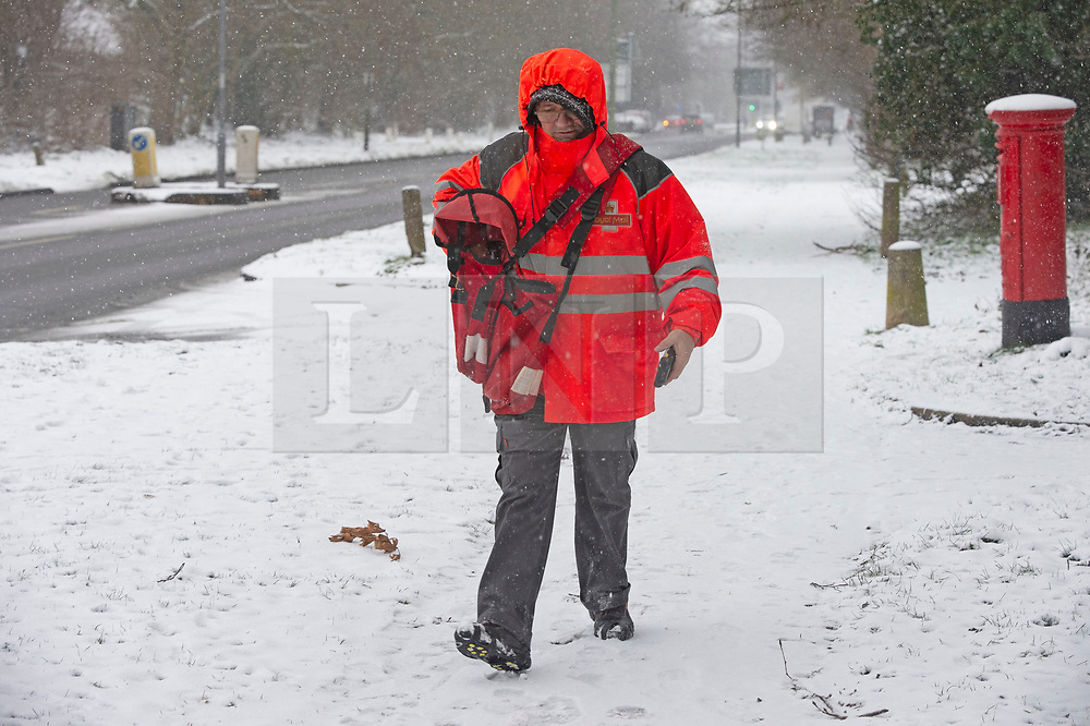 © Licensed to London News Pictures 08/02/2021.        Chelsfield, UK. A postman walking through the snow in Chelsfield, Kent. The Met Office has warned of more freezing cold snowy weather to come with yellow and amber alerts in place for London, Kent and the South East. Photo credit:Grant Falvey/LNP