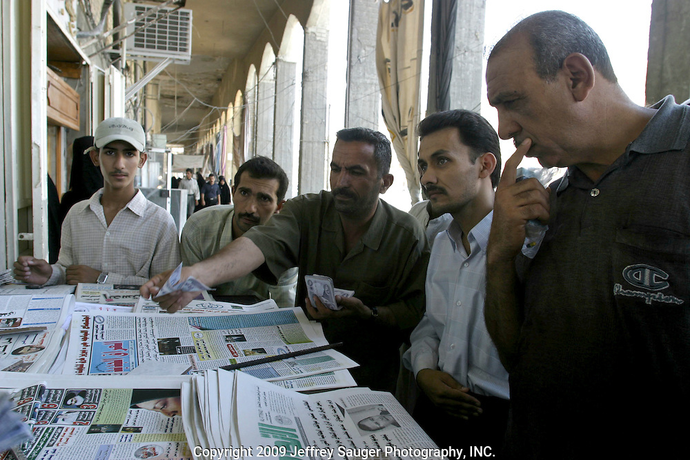 Iraqi men buy newspapers in a market in Karbala, Iraq, Monday, July 21, 2003. There are many more newspapers to choose from since the fall of Saddam Hussein's government as there is much more freedom of speech and expression throughout the country.