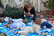 A female volunteer plays with babies and toddlers in the play garden at Princess Alice's Adoption home which is a children's home in association with Bigshoes Foundation, Johannesburg, South Africa.