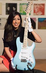 London, September 24th 2015. A Sotheby's worker poses with Eric Clapton's Fender Stratocaster, featured in an exhibition running 24th - 28th September ahead of an auction on September 29th. The exhibition gathers together lyrics, instruments, stage costumes and artworks from some of the world's greatest pop and rock performers and groups, including Abba, The Beatles, Bob Dylan, Pink Floyd and Bruce Springsteen.