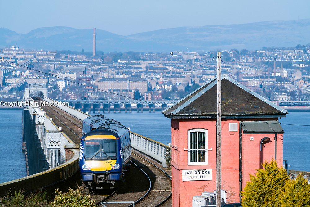 View of Scotrail diesel passenger train travelling towards Dundee across the Tay Rail Bridge at Wormit in Tayside, Scotland, United Kingdom