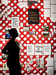 Yorkshire Sculpture Park (YSP) employee Kerry Chase is silhouetted against a latticework wall of photos and words at the YSP unveiling of their new Common Ground exhibition at the YSP in West Bretton, West Yorkshire.