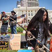 """Carrie Sage Curley, San Carlos Apache, dances to music played by fellow members of the San Carlos Apache Tribe and their supporters in front of the United States Capitol to protest the transfer of Apache land to a private Australian-British mining corporation.  In December 2014, a rider to the National Defense Authorization Act handed over Oak Flat to a foreign-owned company looking to mine copper.  The Apache are currently """"occupying"""" Oak Flat, and travelled to D.C. to protest the action.  In response, Rep. Raul Grijalva (D-AZ-3), proposed the Save Oak Flat Act (H.R. 2811) in June, 2015 to repeal the land exchange.  John Boal Photography"""