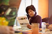 Senior Asian Woman Reading Magazine